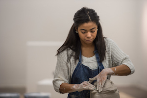 student sculpting with clay
